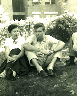 Young Barbara and Elio sitting outside on the grass.