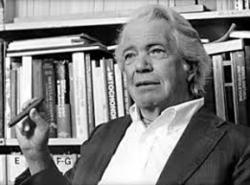 A white-haired man sitting against a bookshelf, holding a cigar.