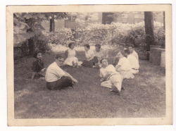 Sepia photo of eight people picnicking on the grass.