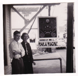 Man and woman, Len and Ruth Hayflick, standing in front of a door with a poster.