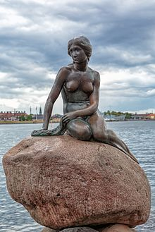 Statue of a mermaid seated on a rock, against the Copenhagen harbor.