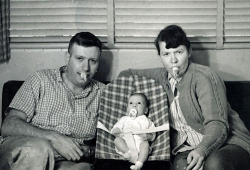 Elio, baby Judith, and Barbara sit on a couch, all with binkies in their mouths.
