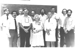 A group of ten men in shirts and ties, behind a small old woman, wearing a white dress and pearls, holding a small trophy or cup.