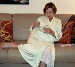 Edith, curled up on a couch, wearing a robe, reading a book.