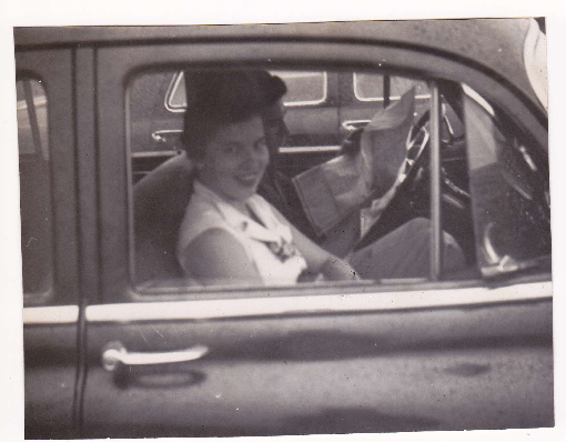 Barbara leaning out the window of a car.