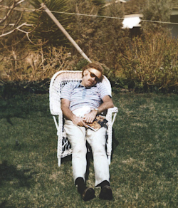 Elio sitting outside in a lawn chair, asleep.
