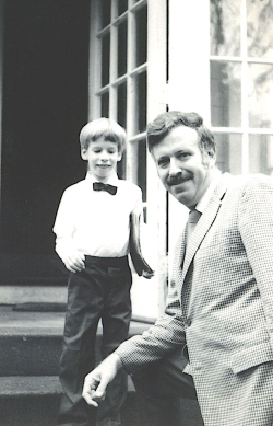 A very small John in a white shirt and bowtie standing on outside stairs next to a seated Elio, wearing a jacket and tie.