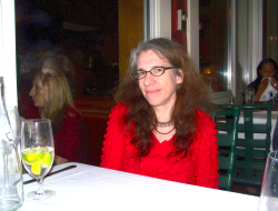 Judith as an adult, wearing a bright red blouse and sitting at a restaurant table.