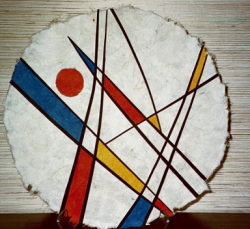 A piece of Edith's artwork: a circle of handmade paper with black lines and curves across it, and blue, red, and yellow solid colors filling in some of the shapes between the intersecting lines.