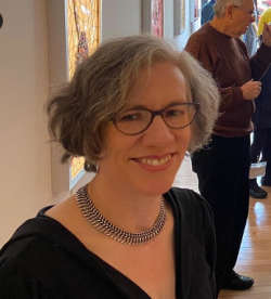 Judith, wearing a black blouse and a necklace, at a gallery with some of her stained glass pieces.